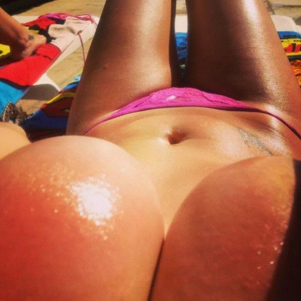 Babe gives a closeup of her huge oily boobs while tanning in bikini.
